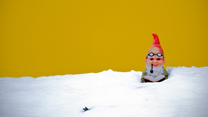 """Garden Gnome sitting in the snow with a book. Public Lecture with Angelika Overath """"From the snow of storytelling"""""""