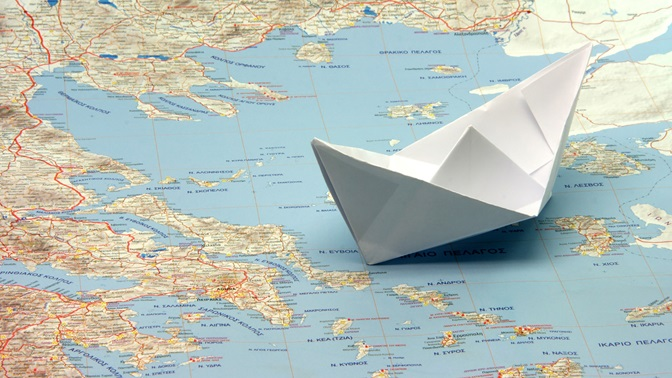 Paper boat on a map betweeten Turkey and Greece