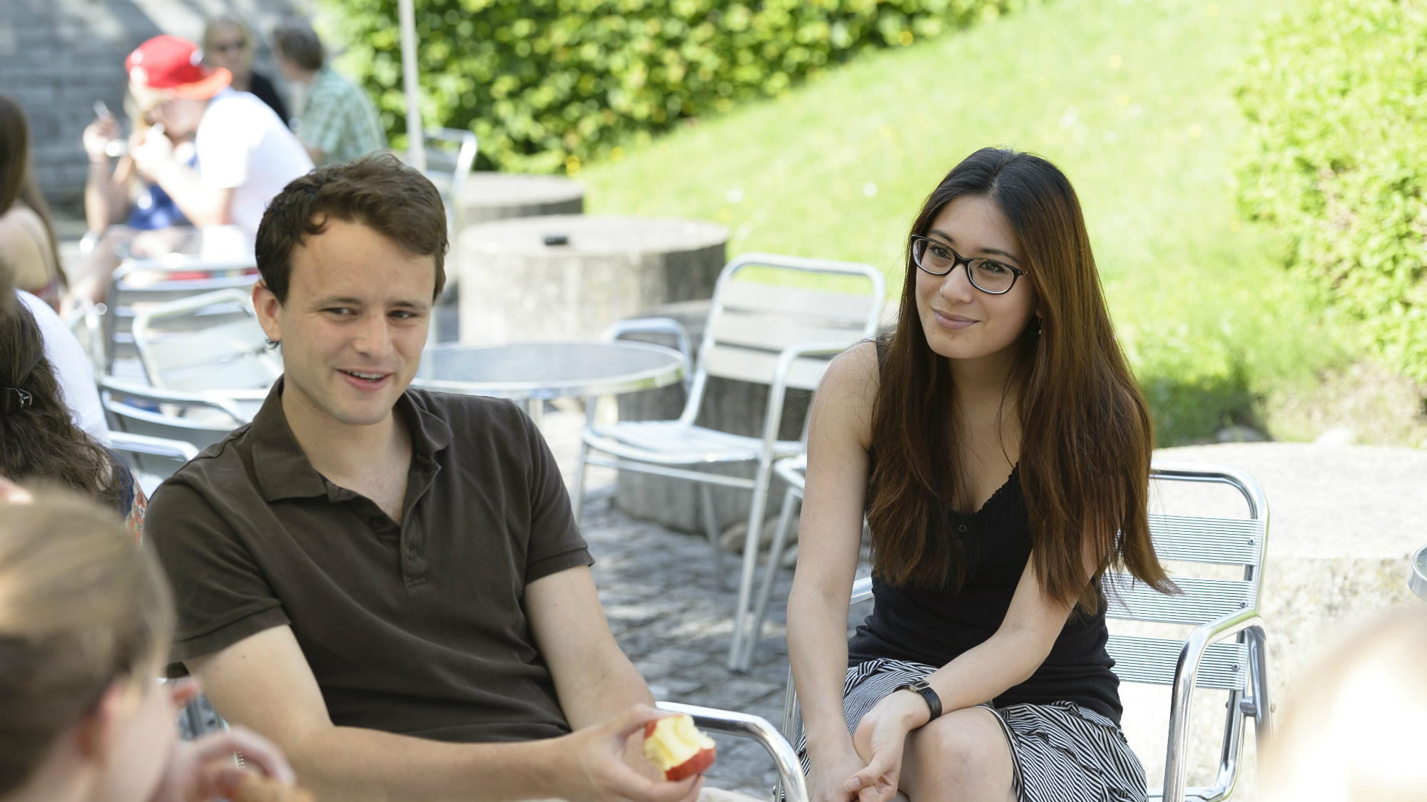 Students sitting outside, enjoying the sun between the Library Building and the Main Building at the University of St.Gallen (HSG)