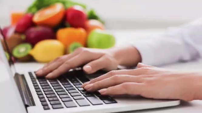 Laptop with fruits in the background
