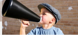 A young boy holds a proportionally big megaphone to his mouth.