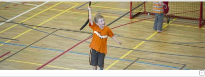 A boy playing Unihockey in the HSG gym