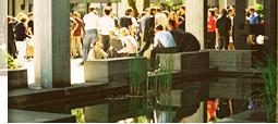 Numerous students meet during their break on the sunny campus in front of the Main Building.