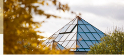 View towards the glass pyramid of the university's Library Building surrounded by an autumnal scenery.