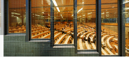 View through the glazed facade into the university's illuminated lecture hall at night.