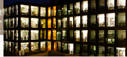View of the glazed facade of the partly illuminated Central Institute Building by night.